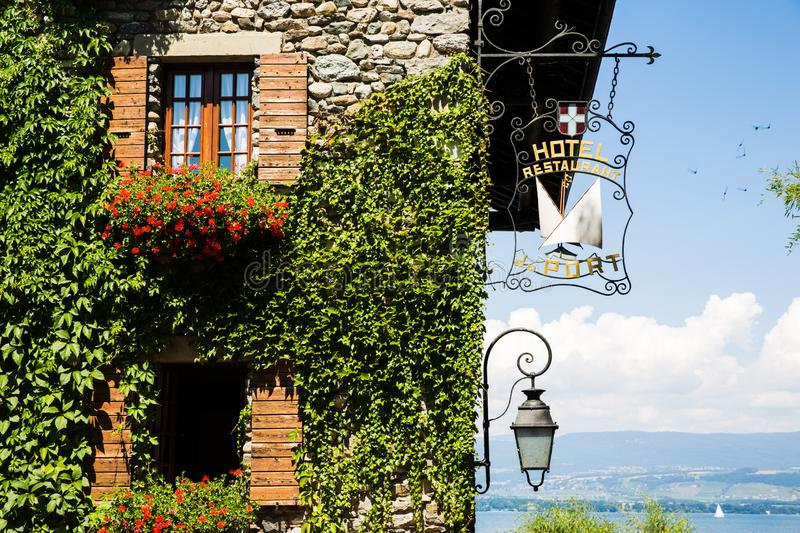 Ivy Covered Stone Wall with Red Flowers, Boats and Lake on a Sun. Ivy Covered Stone House with Red Flowers, Boats and Lake on a Sunny Day stock images