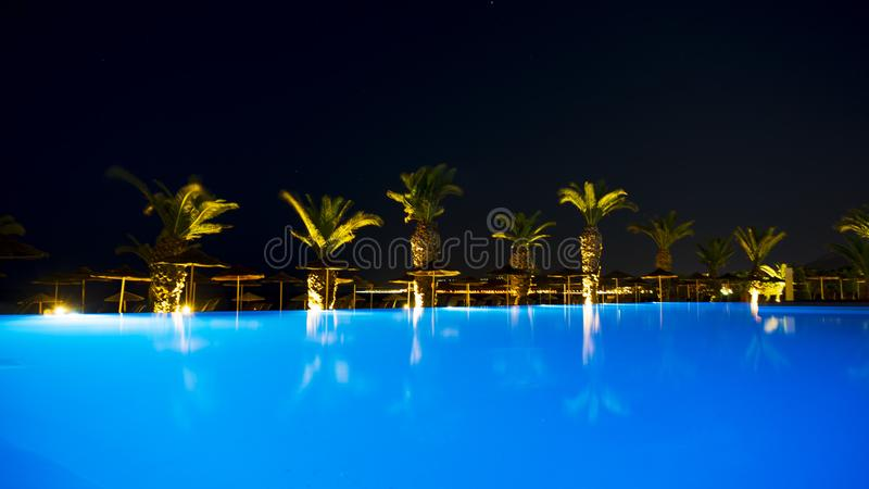 Ixia Grand Hotel Pool in evening light. Ixia Grand Hotel Pool is lit by evening light, with a very nice blue light in the pool, with palm trees in the background stock image