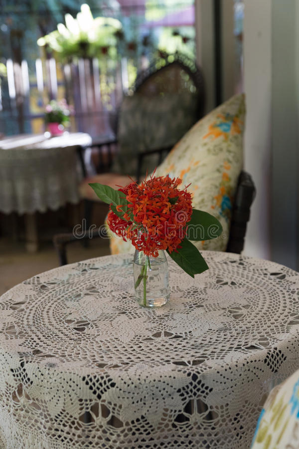 ixora花,在桌,在藤条柴的枕头上的被编织的桌布 免版税库存图片