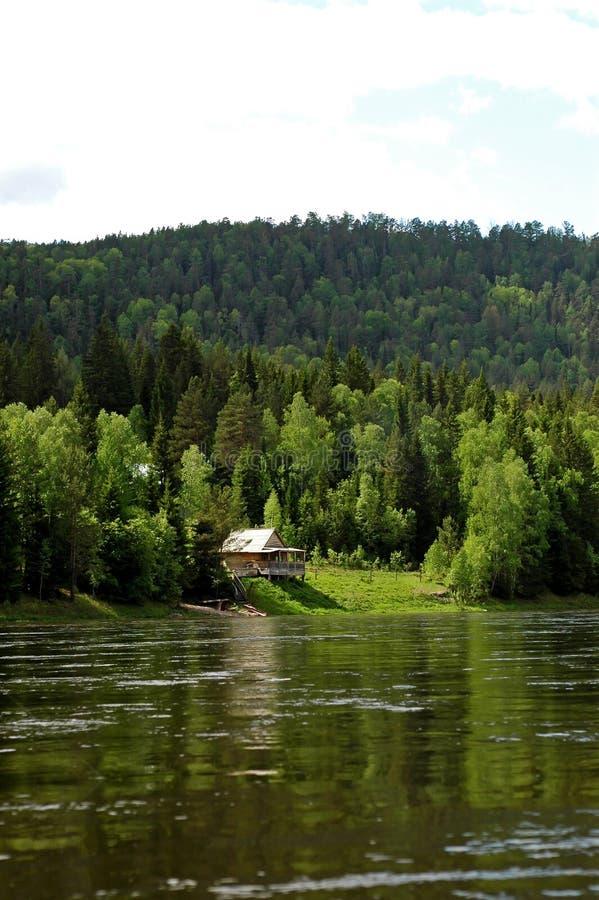 Izba on the Siberian mountain taiga and river Mana royalty free stock photography