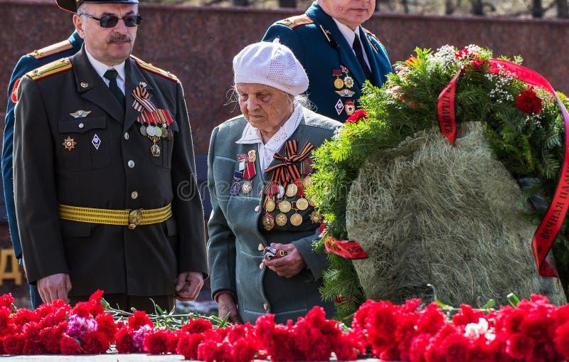 Izhevsk,俄罗斯- 2014年5月9日 40争斗已经来然而荣誉称号比那里更放置内存纪念碑在通过的爱国人位置可能的战士对未知的退伍军人胜利战争几年的日永恒法西斯主义花荣耀了不起的英雄 库存照片