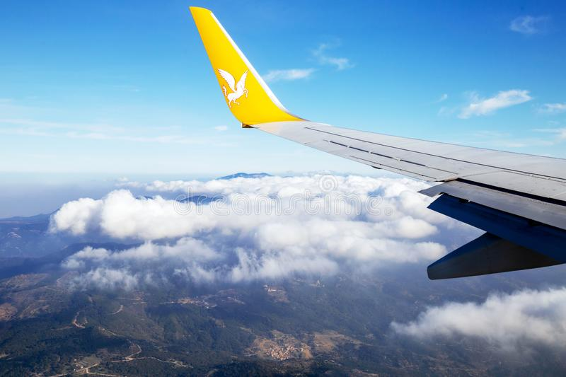 Wing of Pegasus Airlines plane flying over Izmir royalty free stock image