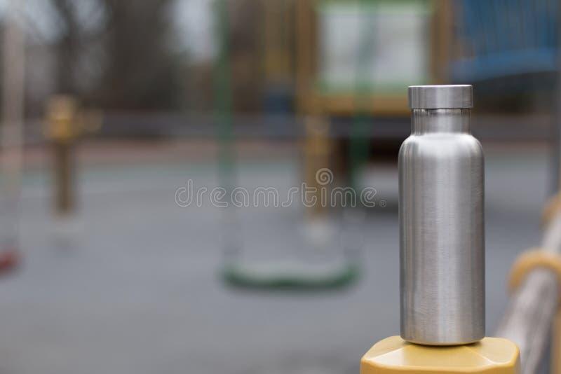 Izolująca Nierdzewna butelka z childrenboiskiem w zimy tle obraz royalty free