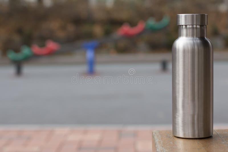 Izolująca Nierdzewna butelka z childrenboiskiem w zimy tle fotografia stock