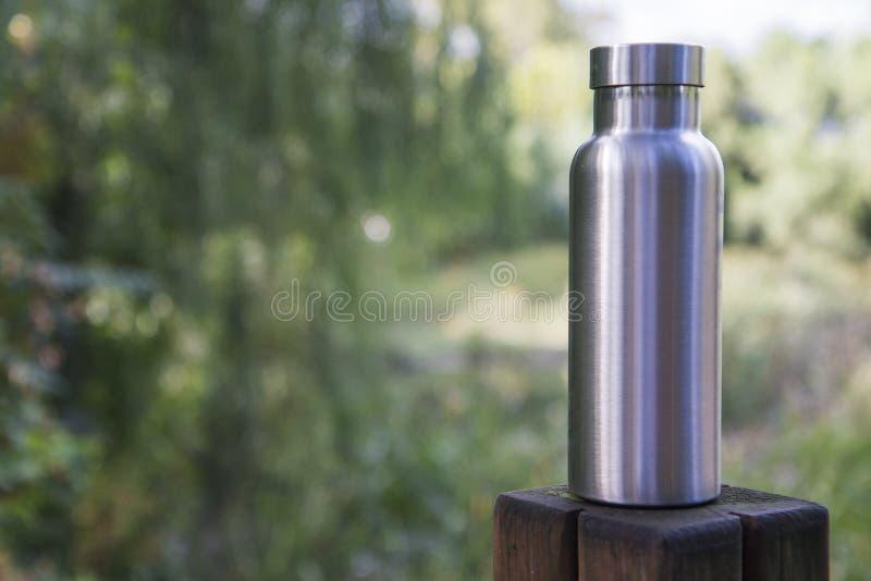Izolująca stali nierdzewnej butelka w lesie fotografia stock