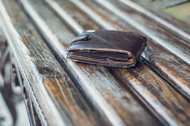 Izquierda una cartera muy vieja del efectivo del bolsillo en un banco de madera en parque público urbano Cosa personal perdida en foto de archivo