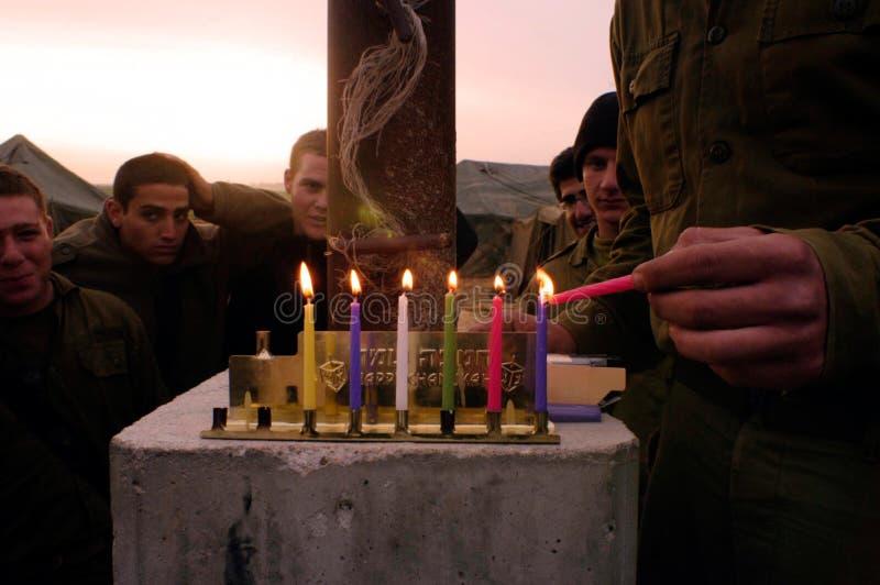 Jánuca - soldados israelíes que encienden un Chanukiah imagenes de archivo