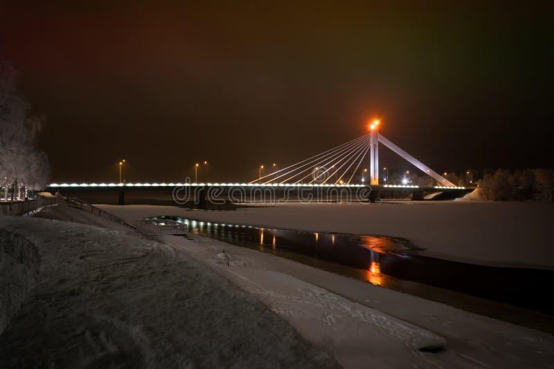 Jätkänkynttilä kabel-gebleven brug over de ijs-behandelde Kemijoki-Rivier stock afbeeldingen