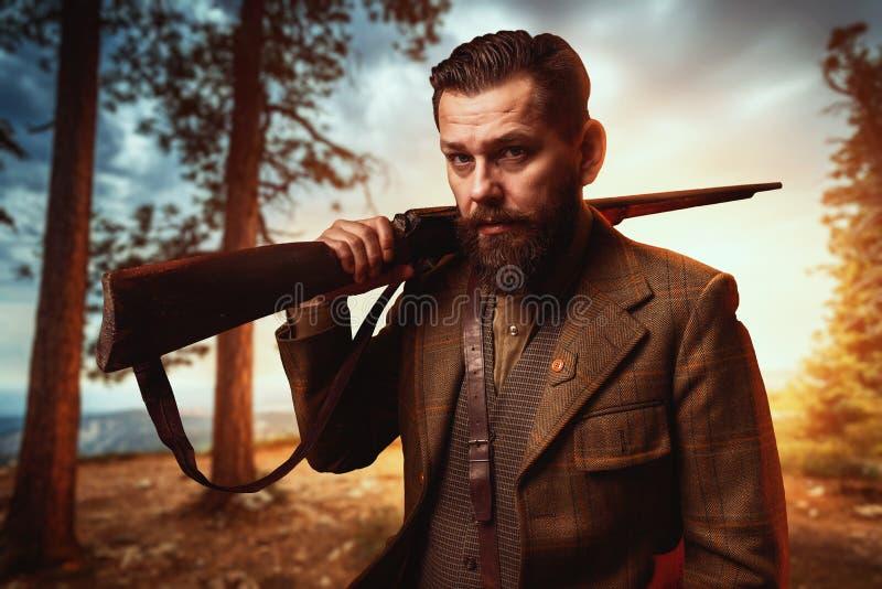 Jägare i tappningjaktkläder med det gamla vapnet royaltyfri foto