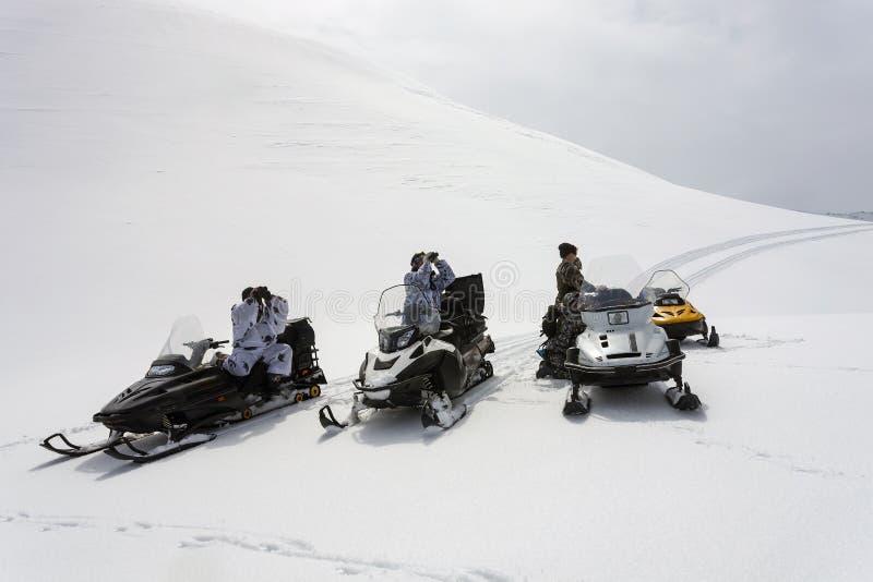 Jägare i vinterkamouflage på snövesslor ser till och med kikare arkivbild