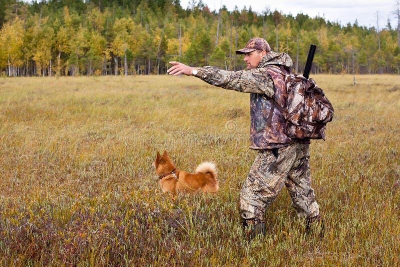 Jägare med hunden på träsket arkivbilder