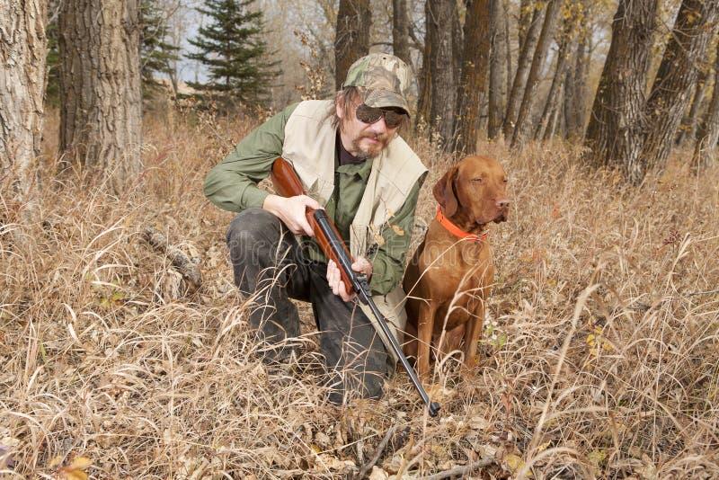 Jägare och hans hund i skogen royaltyfri bild