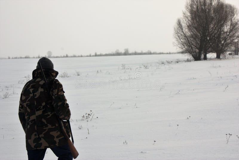 Jägare som går på det snöig fältet i vinter arkivfoto