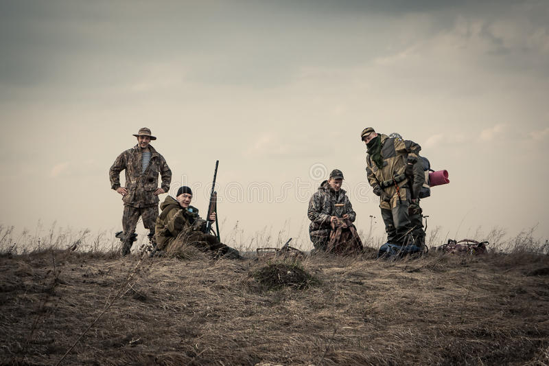 Jägare som tillsammans står mot solnedgånghimmel i lantligt fält under jaktsäsong royaltyfria bilder