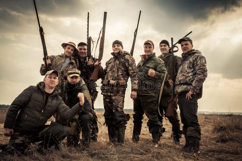 Jägare som tillsammans står mot soluppgånghimmel i lantligt fält under jaktsäsong Begrepp för teamwork royaltyfria bilder