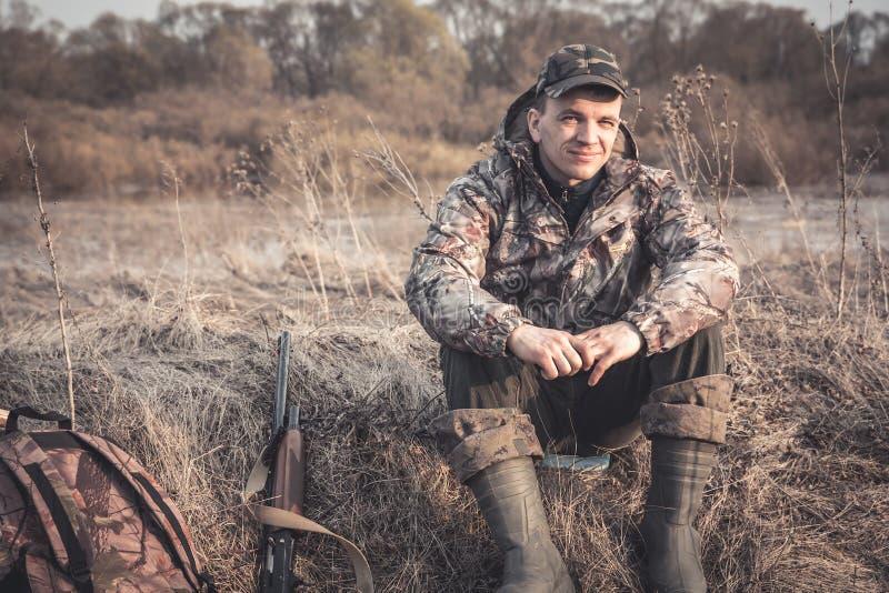 Jägareman i lantligt fält med hagelgeväret och ryggsäcken under jaktsäsong arkivbilder
