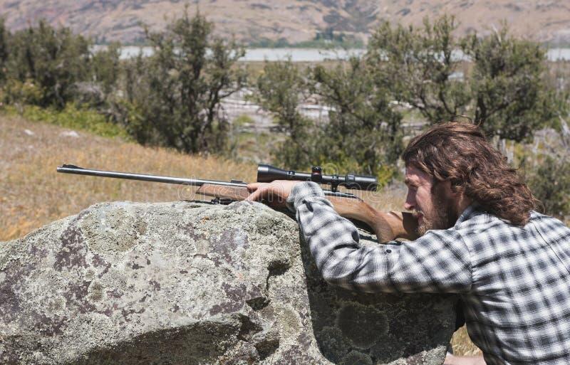 Jäger, der durch das Bereichgewehr schaut stockfotos