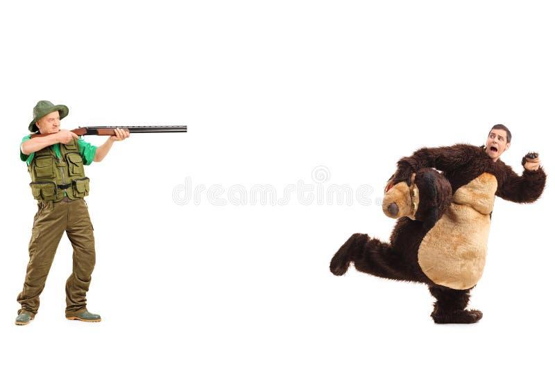 Jäger, der Gewehr in Richtung zum Mann im Bärnkostüm zielt stockbild