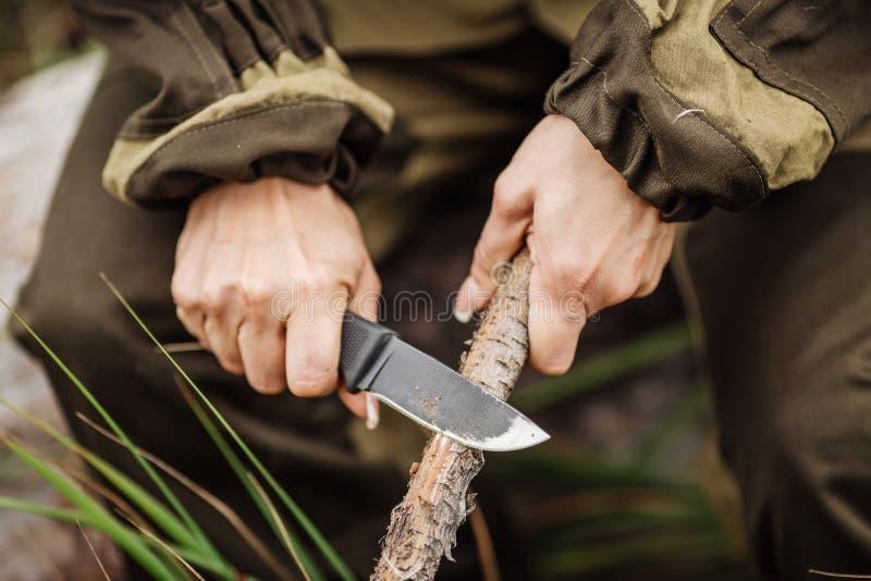 Jäger der jungen Frau mit einem Messer schnitt einen hölzernen Stock stockfotos