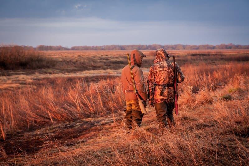 Jäger, die auf Opfer während der Jagd auf dem ländlichen Gebiet während des Sonnenaufgangs aufpassen lizenzfreies stockfoto