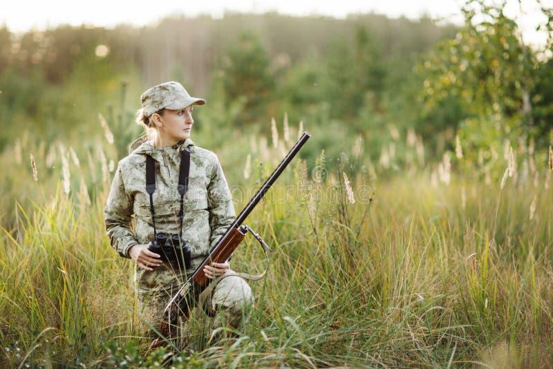 Jäger mit der Schrotflinte, die durch Ferngläser im Wald schaut stockfoto