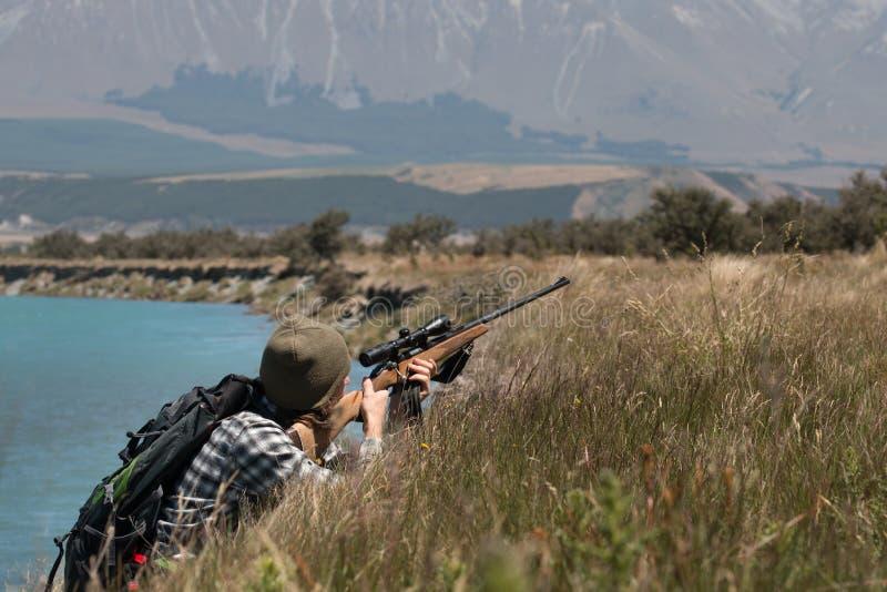 Jäger mit einem Gewehr am Flussufer stockfotos