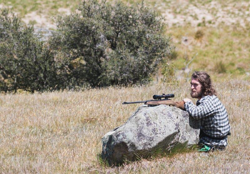 Jäger mit einem Gewehr sitzt nahe Flussstein stockbilder