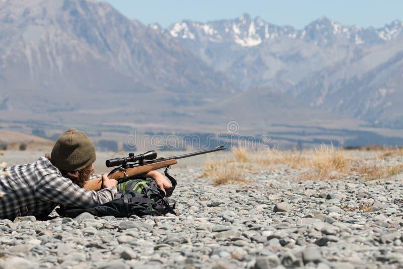 Jäger mit Riffle auf Hintergrund von Bergen lizenzfreie stockbilder