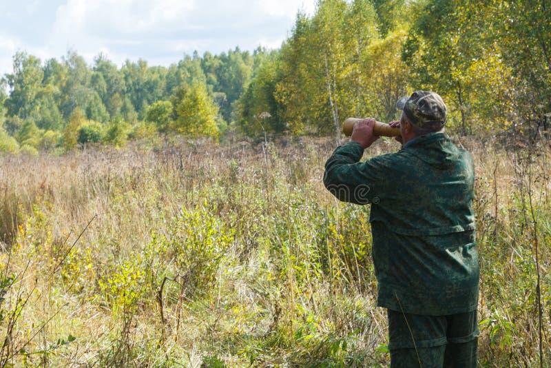 Jäger nennt einen Elch während der Furchenjagd lizenzfreie stockfotografie