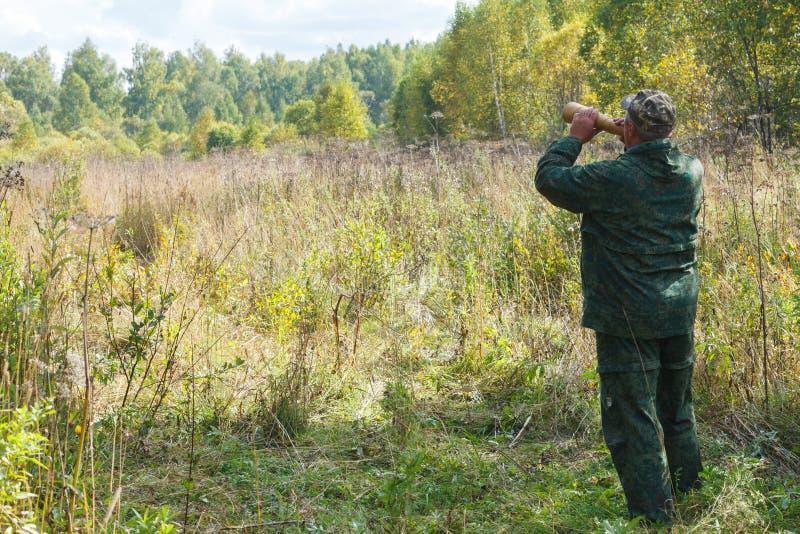 Jäger nennt einen Elch während der Furchenjagd lizenzfreie stockbilder