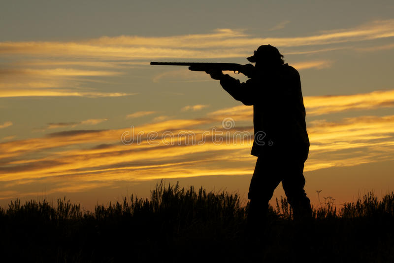 Jäger-Schießen im Sonnenuntergang lizenzfreies stockbild
