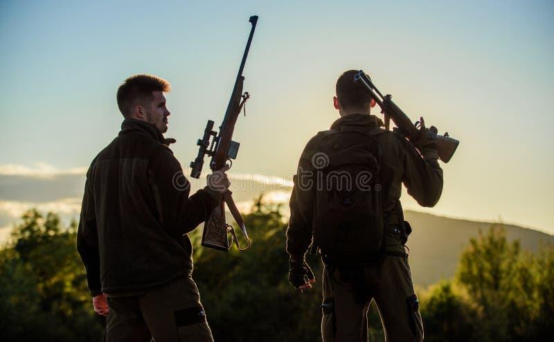 Jägerfreundwildhüter mit Gewehren silhouettieren Himmelhintergrund Jägergewehr-Naturumwelt Der war großer Tag stockbild