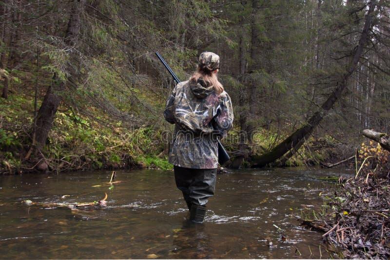 Jägerin, die den Fluss kreuzt stockfoto