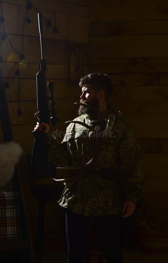 Jägerkonzept Mann mit Bart trägt Tarnungskleidung, dunklen Hintergrund Macho auf strengem Gesicht am Wildhüterhaus stockfoto