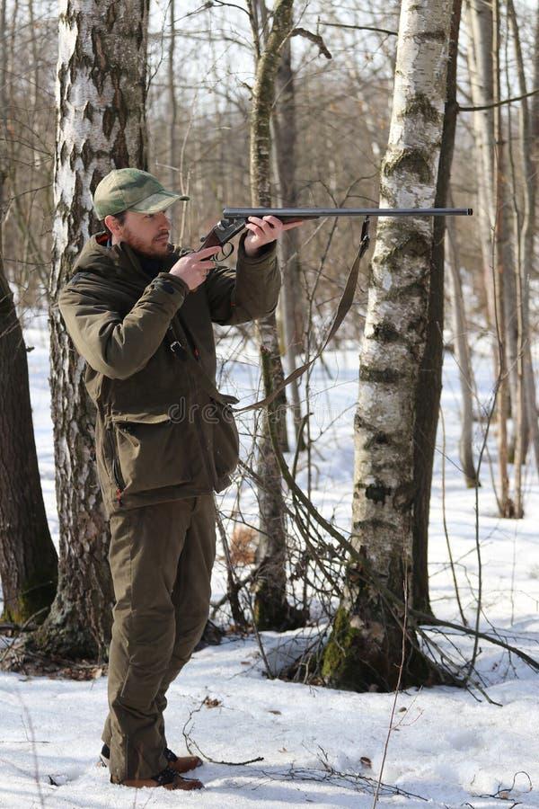 Jägermann in der dunklen kakifarbigen Kleidung im Wald stockfotos