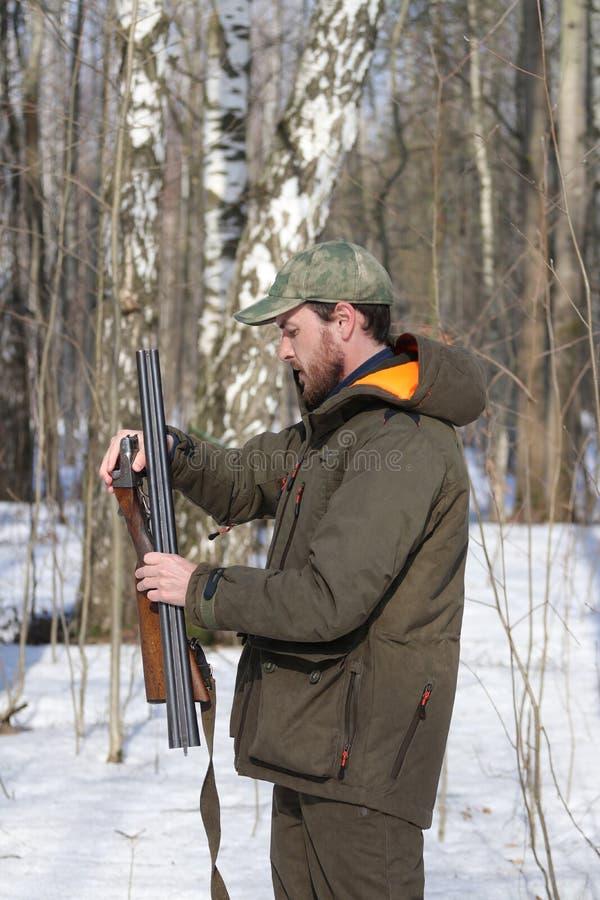 Jägermann in der dunklen kakifarbigen Kleidung im Wald lizenzfreies stockbild