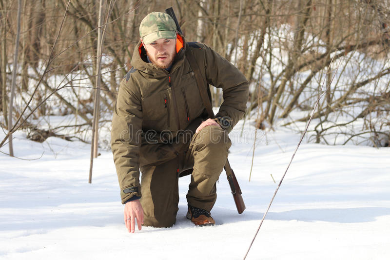 Jägermann in der dunklen kakifarbigen Kleidung im Wald stockbild