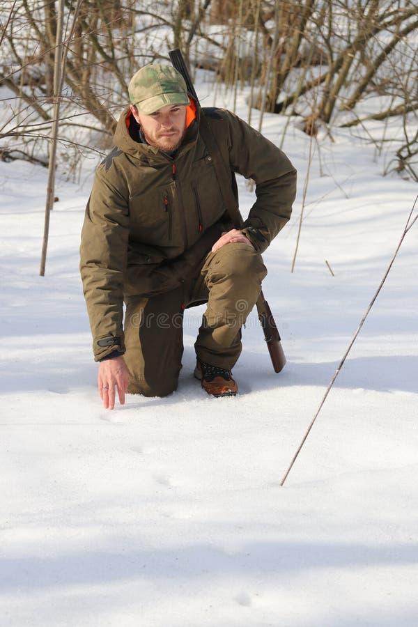 Jägermann in der dunklen kakifarbigen Kleidung im Wald stockbilder