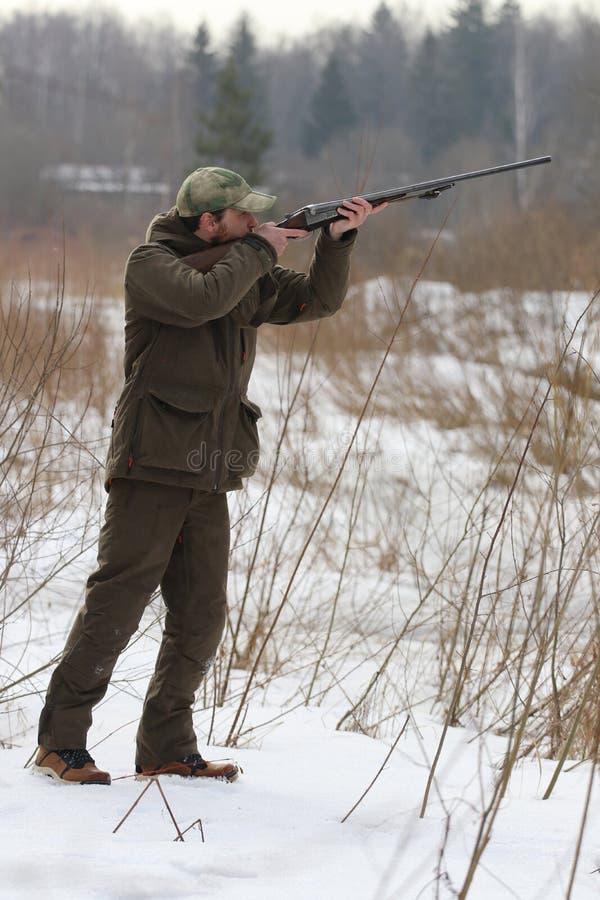 Jägermann in der dunklen kakifarbigen Kleidung im Wald lizenzfreie stockfotografie