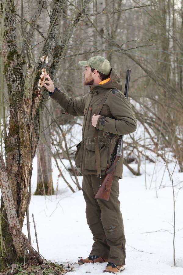 Jägermann in der dunklen kakifarbigen Kleidung im Wald lizenzfreie stockfotos