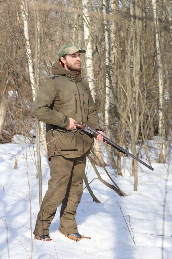Jägermann in der dunklen kakifarbigen Kleidung im Wald lizenzfreies stockfoto