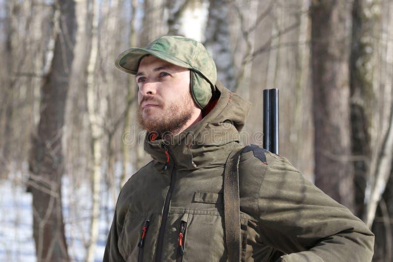 Jägermann in der dunklen kakifarbigen Kleidung im Wald stockfotografie