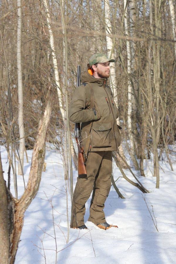 Jägermann in der dunklen kakifarbigen Kleidung im Wald stockfoto