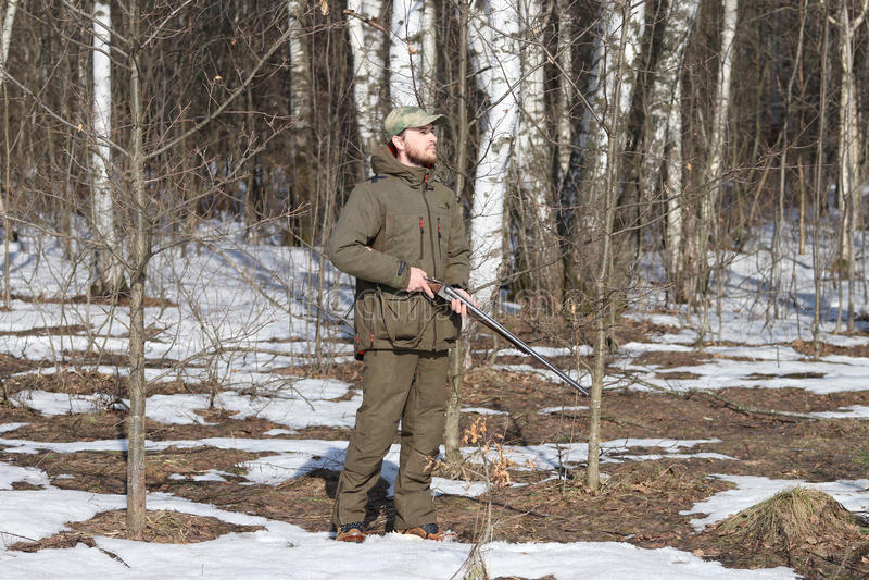 Jägermann in der dunklen kakifarbigen Kleidung im Wald lizenzfreie stockbilder