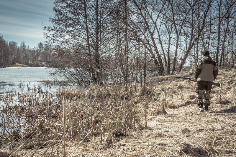 Jägermann, der entlang Flussbank während der Frühlingsjagdsaison geht lizenzfreies stockbild