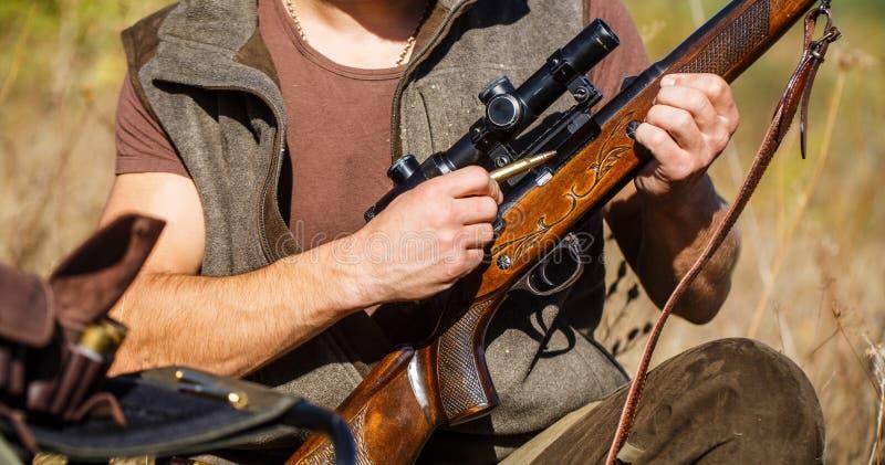 Jägermann Jagd des Zeitraums Mann mit einem Gewehr, Gewehr Mann lädt ein Jagdgewehr auf Abschluss oben Prozess von Jagd während lizenzfreies stockbild