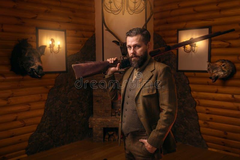 Jägermann mit altem Gewehr gegen antiken Kasten lizenzfreies stockbild
