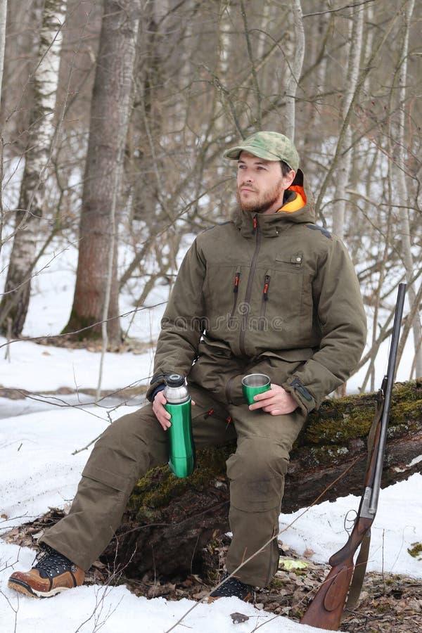 Jägermann trinkt Rest und trinkenden Tee im Wald stockfotografie