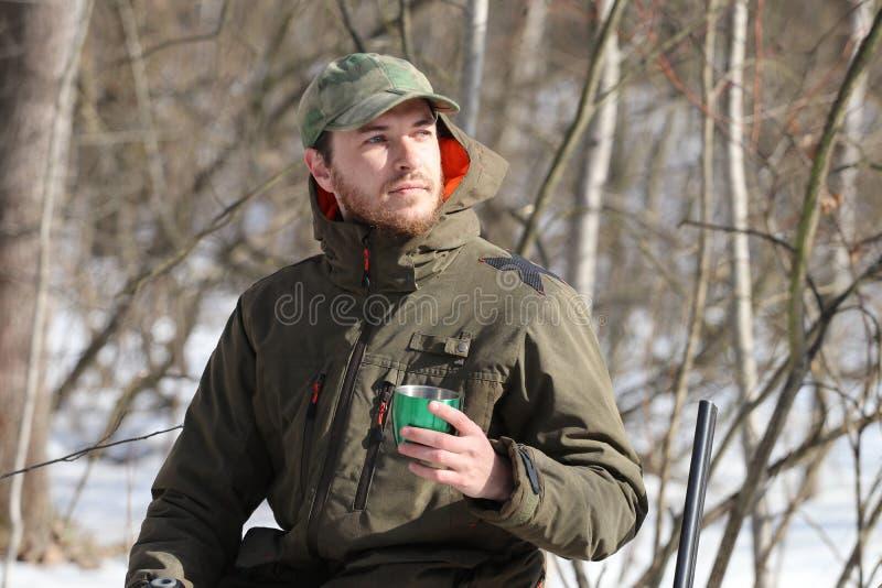 Jägermann trinkt Rest und trinkenden Tee im Wald lizenzfreie stockfotos