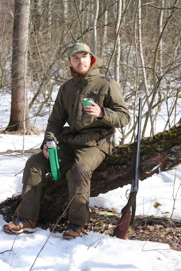 Jägermann trinkt Rest und trinkenden Tee im Wald lizenzfreies stockfoto